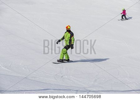 Man in a green jumpsuit snowboarding on snow in the mountains on small child skiing in the background
