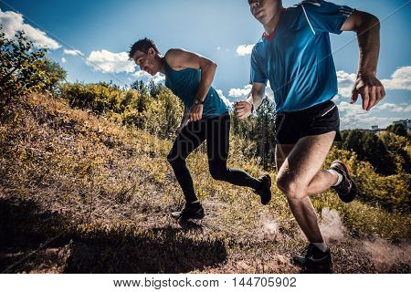 Two athlete crossing off road terrain at sunny day