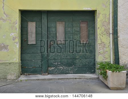 An old wooden door in Marano Lagunare in Friuli Venezia Giulia north east Italy.