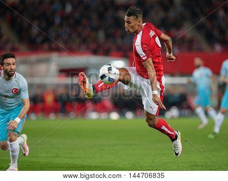 VIENNA, AUSTRIA - MARCH 29, 2016: Rubin Okotie (Austria) kicks the ball in a friendly football game.
