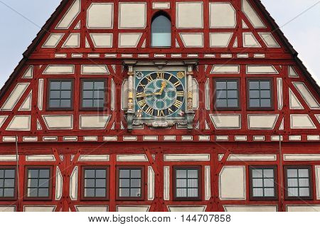 Red half-timbered Town Hall. Front facade fragment with ancient clock. Besigheim, Baden-Wurttemberg, Germany
