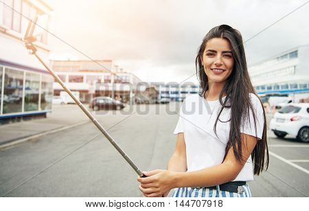 Smiling young adult woman in white shirt blue striped pants and long brown hair holding selfie stick with camera on other end taking her picture