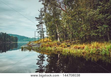Beautiful autumn landscape with lake pine trees natural stone coast in the Republic of Karelia Ladoga Lake northern region in Russia. Fall forest russian tourism and travel concept.