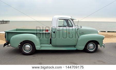 FELIXSTOWE, SUFFOLK, ENGLAND - AUGUST 27, 2016: Classic Green and White  Chevrolet 3100 pickup truck on seafront promenade.