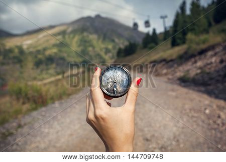 Hand With Compass In The Mountains