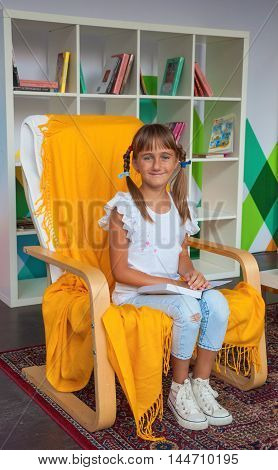 Smiling cute girl sitting in a chair in the library with a book in their hands