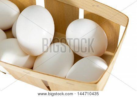 Chicken eggs in basket on white background