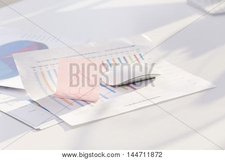Desktop with annual reports and sticky note with a heart on it