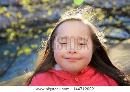 Portrait of little girl smiling outside .