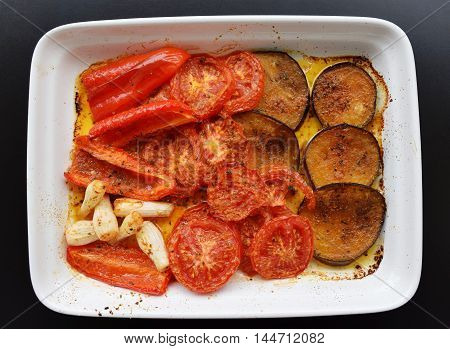 Grilled vegetables eggplant, peppers and tomatoes on white dish