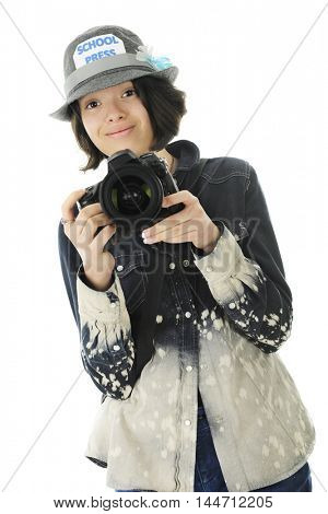 A pretty young school photographer looking at the viewer with her camera at the ready.  On a white background.
