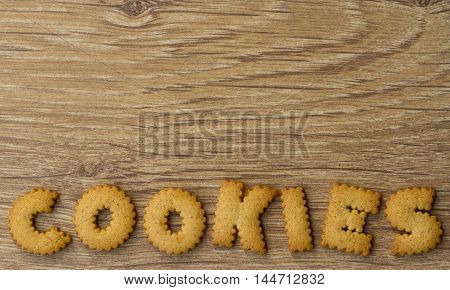 The word cookies spelled out with small alphabet  biscuits on a wooden table top with copy space above.