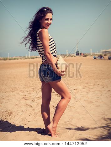 Beautiful Smiling Woman With Fashion Bag Posing On The Beach Background In Denim Shorts. Toned Portr