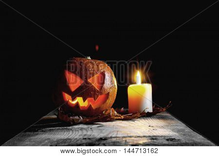 Halloween pumpkin head and candle on wooden table over black background