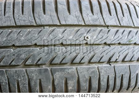 close up of screw nail puncturing damage tire