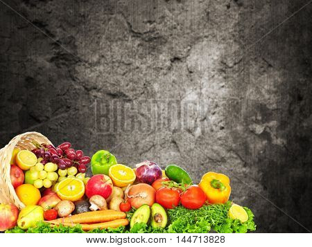 Vegetables and fruits over dark wall background.