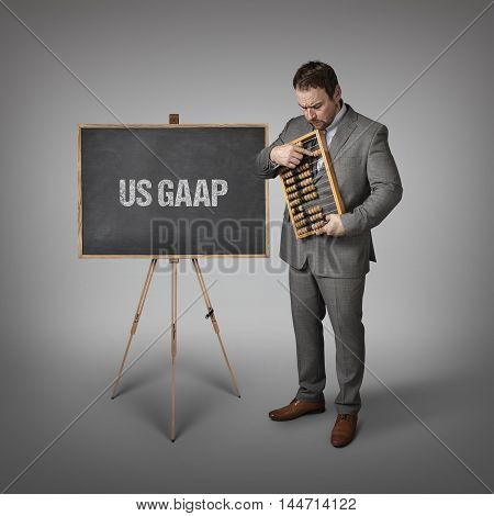 US GAAP text on blackboard with businessman and abacus