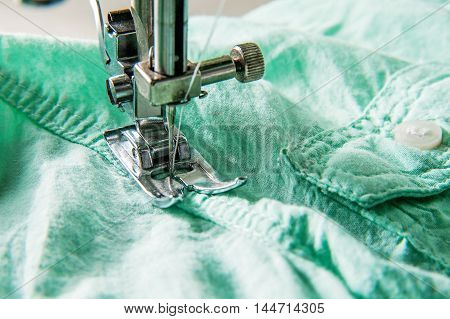 Closeup of sewing machine working part with green cloth