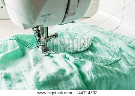 parth of sewing machine with green textile closeup