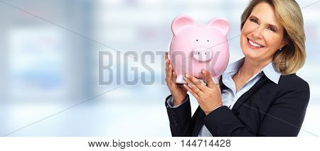 Senior business woman with a piggy bank.