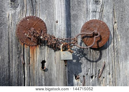 Closed wooden door with old lock and chain