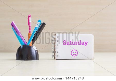 Closeup color pen with black ceramic desk tidy for pen and purple saturday word in white page and happy face emotion at the note book on blurred wood desk and wood wall textured background