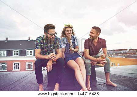 Two handsome men and a beautiful young woman drinking beer while sitting on roof in city