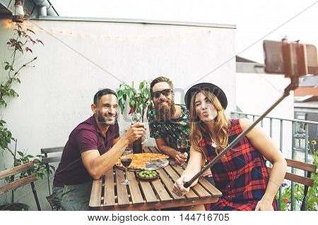 Trio of young joyful European friends sitting together at table with large pizza and wine glasses posing for camera phone on selfie stick