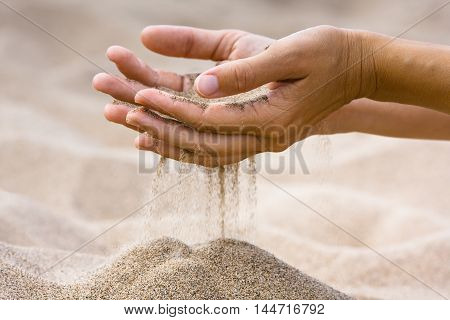 sand running through fingers of woman in the beach