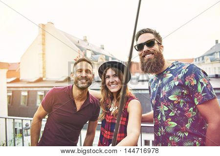 Woman and two male friends stand on patio and smile towards the camera as she makes bunny ears on one of them