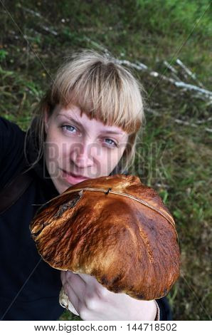 Beauty woman in a forest picking up big mushroom closeup