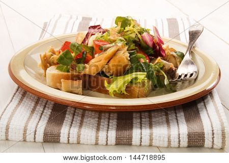 fresh smoked scottish mackerel salad with tomato chopped onion and sliced bread on a plate