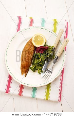 gently smoked scottish mackerel with lemon and and salad fork and knife on a plate