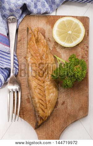 gently smoked scottish mackerel with lemon and parsley on a wooden board