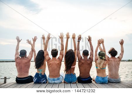 Back view of multiracial group of young people sitting on pier with raised hands