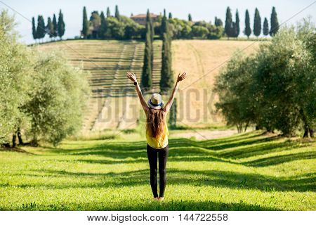 Young woman in hat and yellow shirt enjoying beautiful Tuscan landscape in Italy.