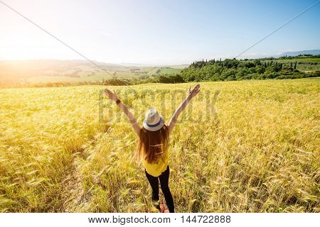 Young woman in hat and yellow shirt standing in the wheat field. Enjoying beautiful Tuscan landscape in Italy.