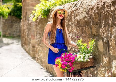 Beautiful woman in blue dress and hat standing with retro bicycle full of flowers in the old italian town