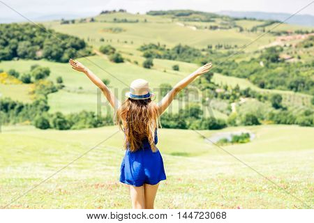 Young woman in blue dress and hat with raised hands enjoying beautiful Tuscan landscape in Italy.