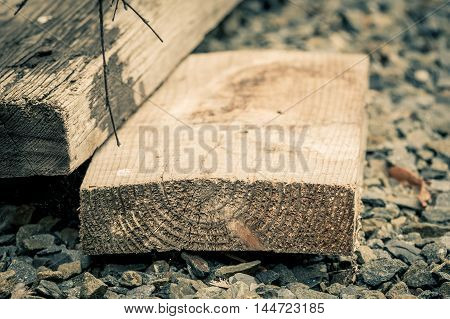 Aged wooden planks on stones in shallow depth of field