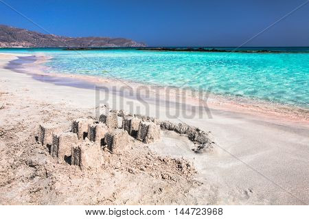 The wave of the sea on the pink sand and beautiful beach with the sand castle.Coast of Crete island in Greece. Pink sand beach of famous Elafonisi (or Elafonissi).