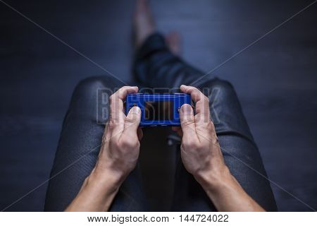 Gothenburg, Sweden - August 29, 2016: A shot from above of a young mans hands holding a Game Boy Micro portable video game console developed by Nintendo Co., Ltd.