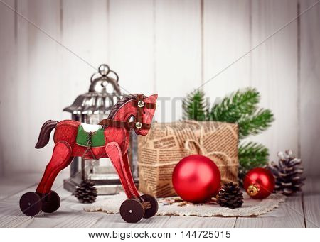 Christmas wooden decoration in retro style new year still life with tinsel gift and branch firtree on old board