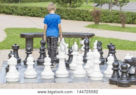 Outdoor chess game using life sized chess pieces and chess board. Boy plays in the park
