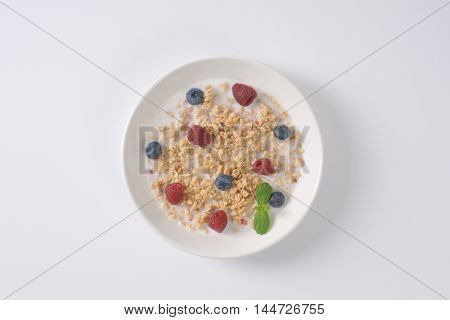 plate of granola with milk for healthy breakfast on off-white background with shadows