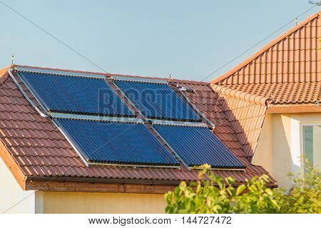 Vacuum collectors- solar water heating system on red roof of the house
