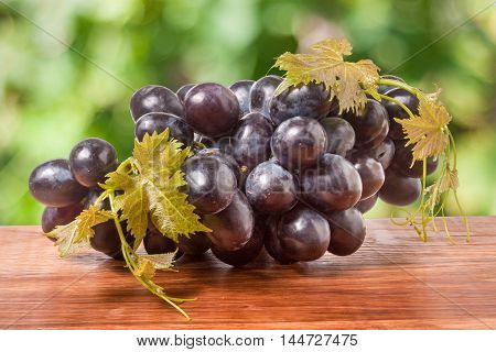 bunch of blue grapes on a wooden table with a blurred background.