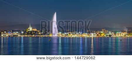 Panoramic of Geneva skyline and fountain at night.