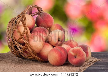 peaches in a wicker basket on a wooden table with a blurred background.