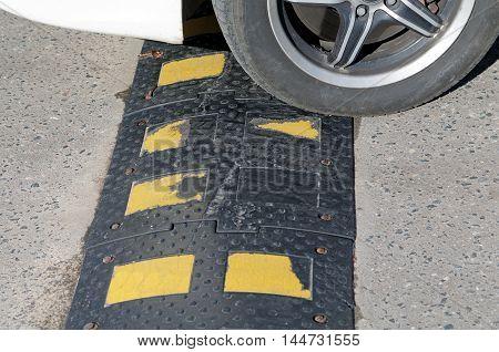 car tire encounters a sleeping policeman summer